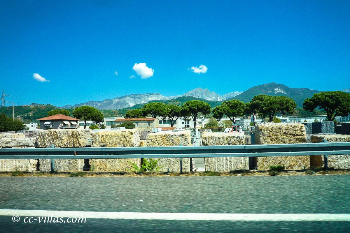 Carrara Marmor - Von der Autobahn gesehen: Im Hintergrund die Marmorberge und davor die rohen Marmorblöcke.