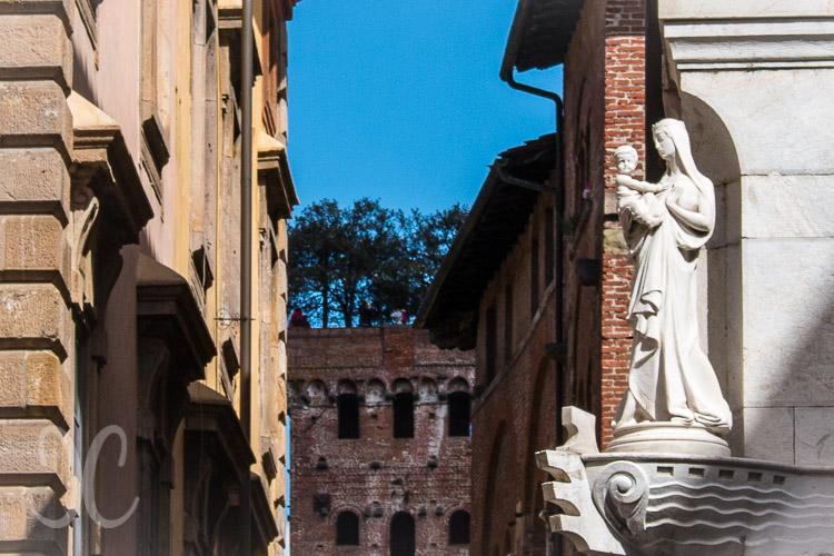 Torre Guinigi in einer Straßenschlucht und davor die Madonna